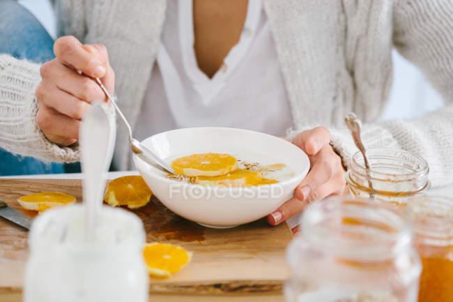 Immagine potata della donna che mangia muesli con orange per la colazione — Foto stock
