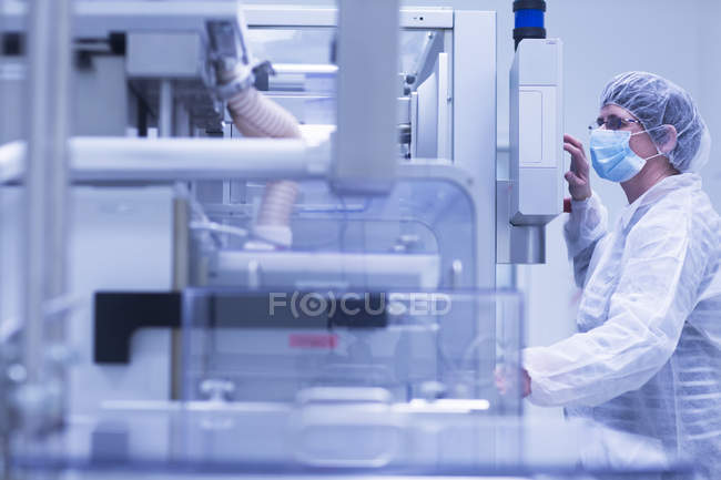 Worker operating machinery in pharmaceutical plant — Stock Photo