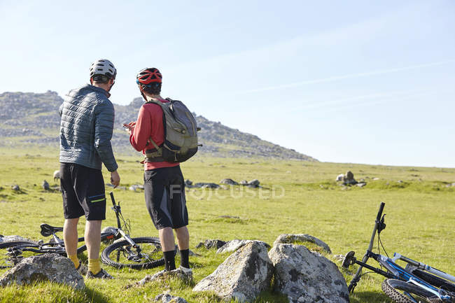 Cyclists on hillside chatting — Stock Photo