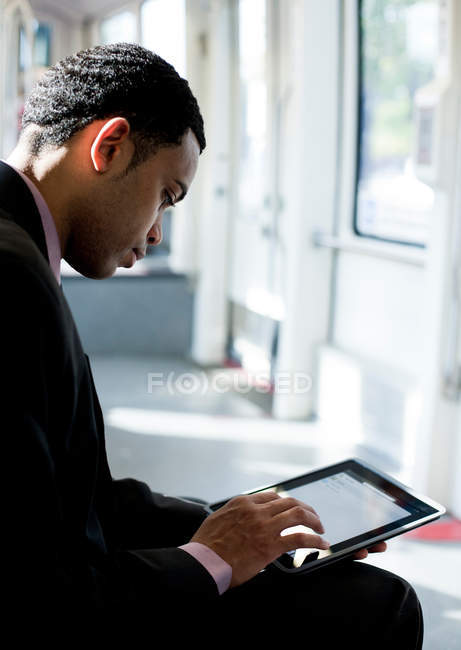 Бизнесмен с использованием цифрового планшета на поезде — стоковое фото