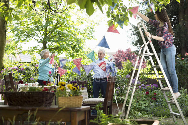 Grandparents and granddaughter hanging up bunting — Stock Photo