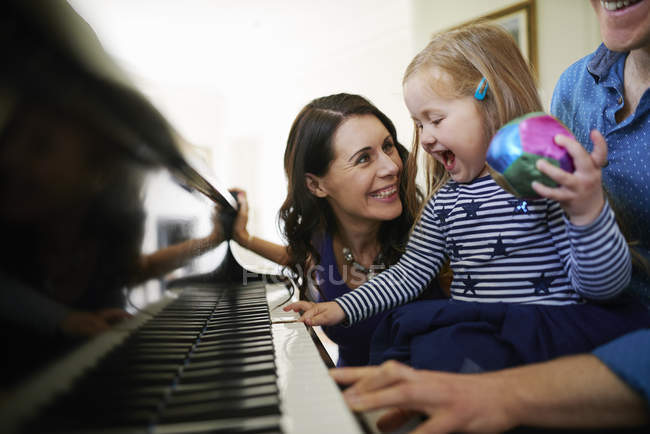 Parents teaching daughter to play piano — Stock Photo