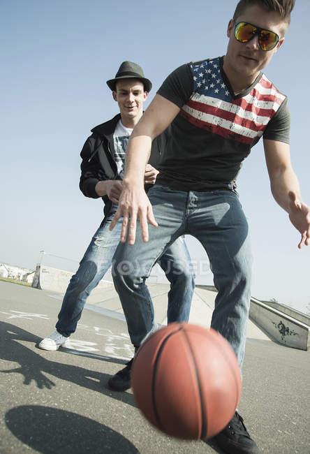 Молоді чоловіки грають в баскетбол в скейтпарк — стокове фото
