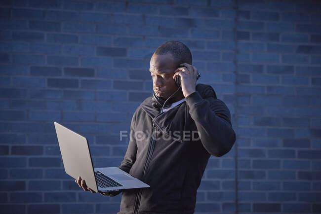 Чоловік, що тримає ноутбук, слухає навушники. — стокове фото