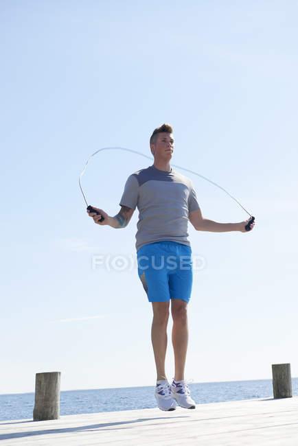 Людина на пристані, використовуючи пропускаючи мотузку — стокове фото