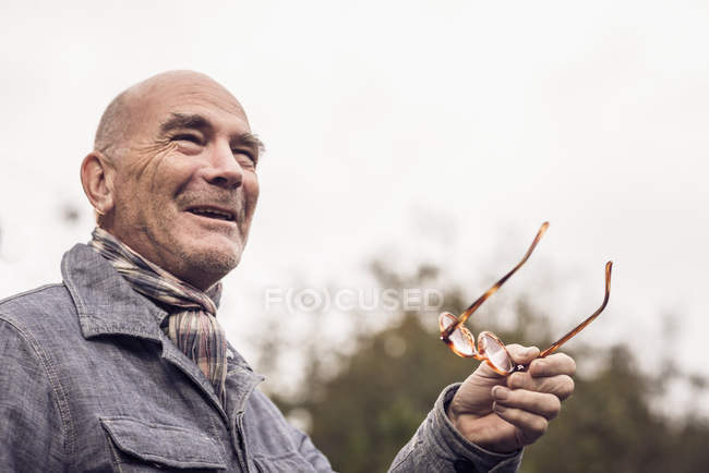 Senior man gesturing with spectacles — Stock Photo