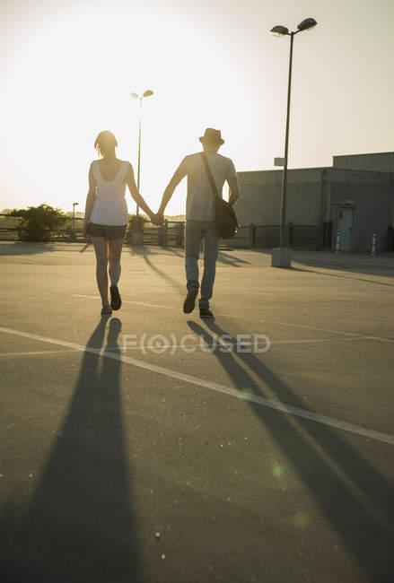 Romantique jeune couple flânant main dans la main à travers un parking vide — Photo de stock
