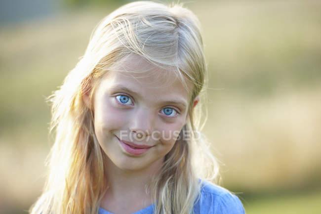 Retrato de una joven sonriente con ojos azules en el campo - foto de stock