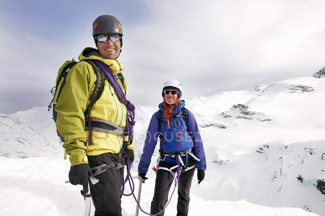 Alpinisti sulle montagne innevate guardando la macchina fotografica sorridente, Saas Fee, Svizzera — Foto stock
