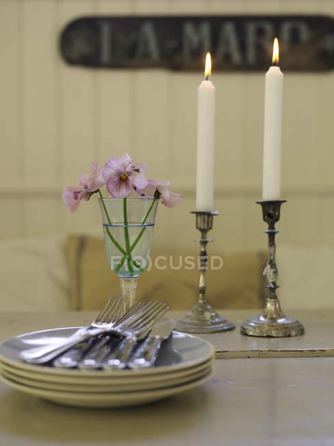 Pratos, talheres e velas acesas na mesa de jantar — Fotografia de Stock
