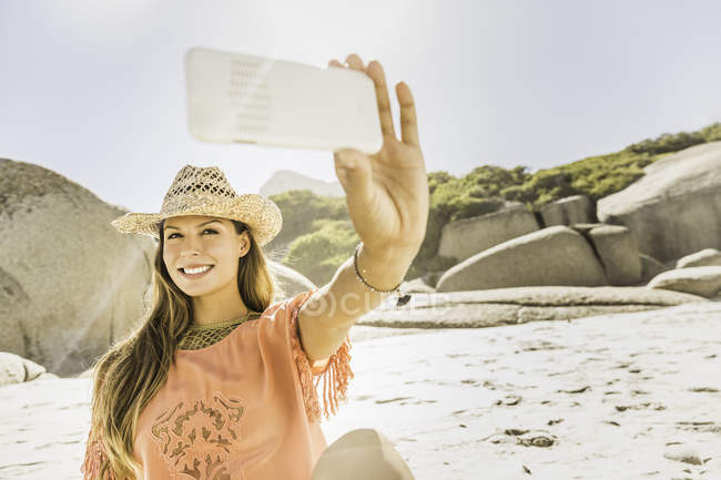 Woman wearing straw hat taking smartphone sellfie on beach, Cape Town, South Africa — Stock Photo