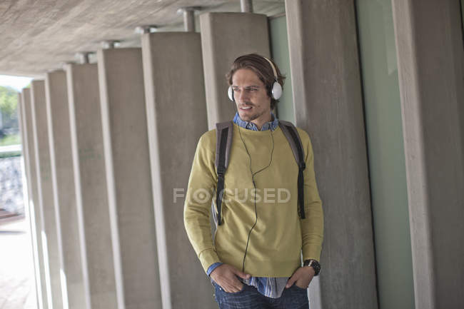 Mid adult man listening to headphones in city underpass — Stock Photo