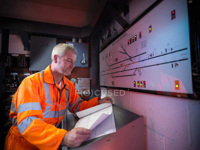 Railway worker checking railway points on illuminated display panel — Stock Photo