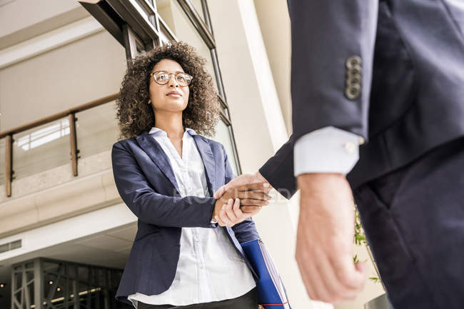 Low angle view of young businesswoman shaking hands with businessman at office — Stock Photo