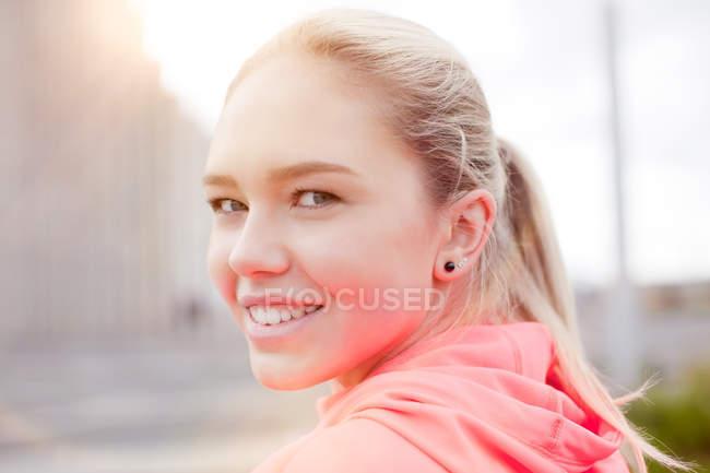 Portrait teenage girl, looking over shoulder at camera, smiling, Reykjavik, Iceland — Stock Photo