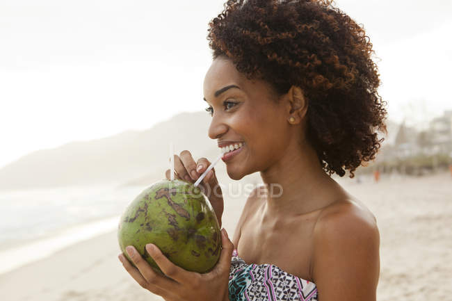 Portrait of young woman drinking coconut milk on beach, Rio De Janeiro, Brazil — Stock Photo