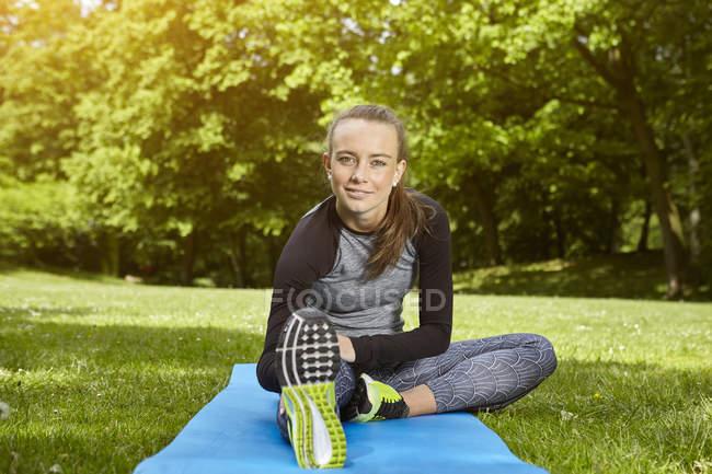 Молодая женщина тренируется в парке, растягивается на тренировочном коврике — стоковое фото