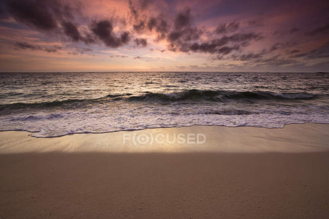 Cloudy sunrise sky over ocean and coastline — Stock Photo