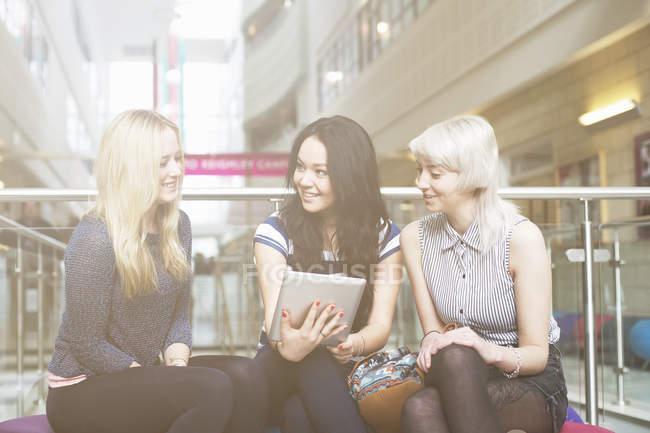 Молодые женщины используют цифровые планшеты в университете — стоковое фото