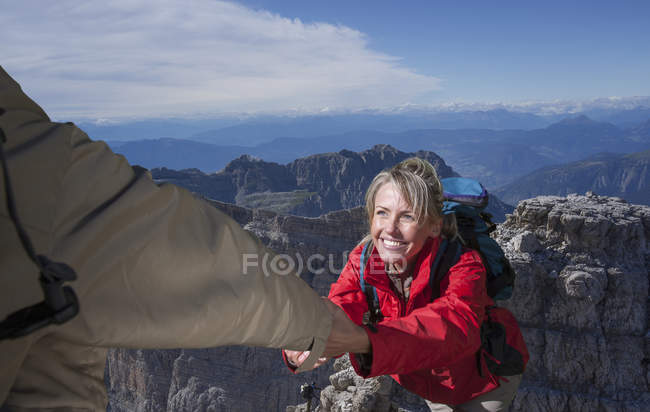 A male climber helping his female partner to reach the top of a mountain, Dolomites, Italy — Stock Photo