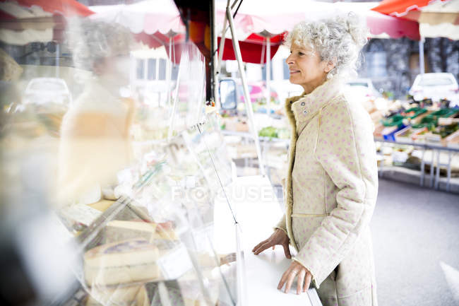 Mature female shopper buying cheese at local french market — Stock Photo