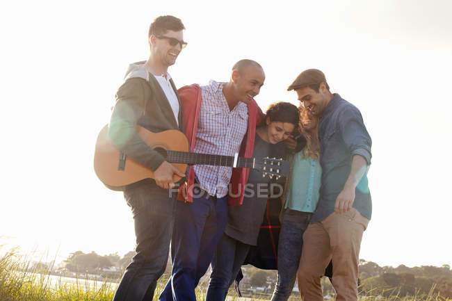 Five friends with acoustic guitar on Bournemouth beach, Dorset, UK — Stock Photo
