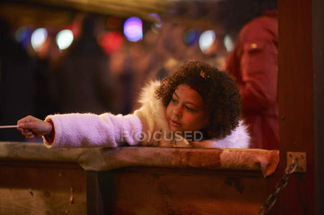 Young girl at funfair, leaning on side of funfair stall — Stock Photo