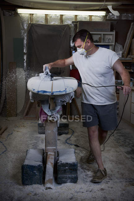 Mature man sanding a surfboard in garage — Stock Photo