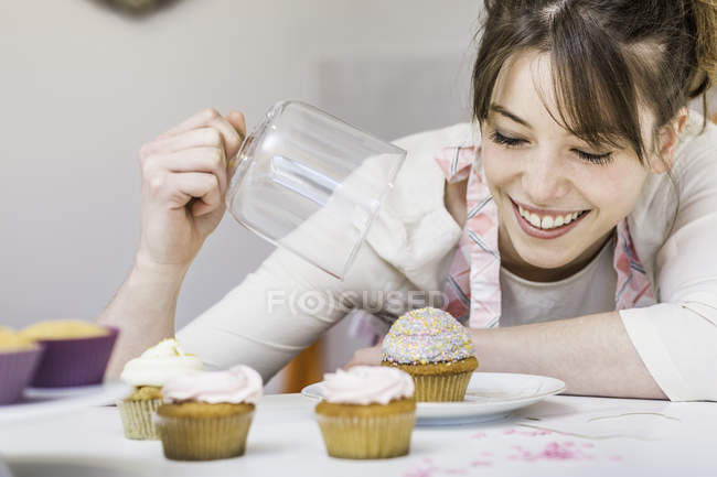 Smiling woman looking at cupcakes in the kitchen — Stock Photo