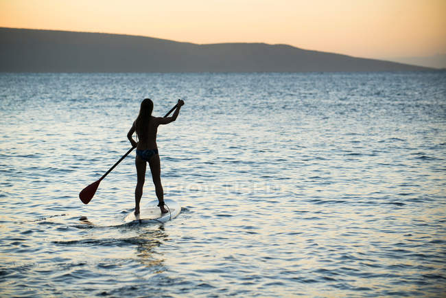 Rear view of woman paddleboarding on ocean surface — Stock Photo