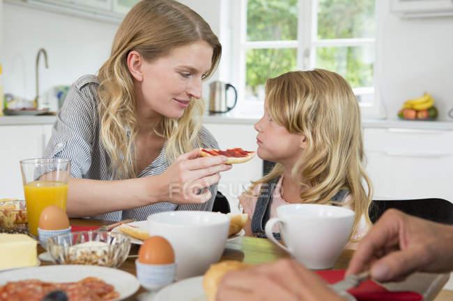 Mãe oferecendo a filha alguma comida em casa — Fotografia de Stock