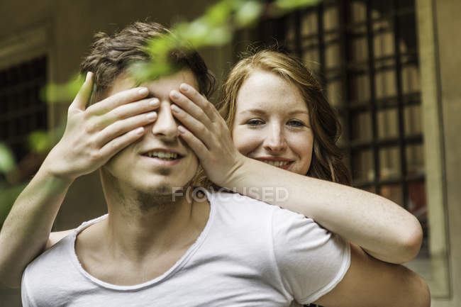 Young woman covering boyfriend's eyes — Stock Photo