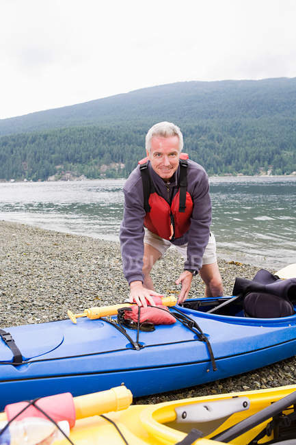 Man with kayak on the beach looking at the camera — Stock Photo