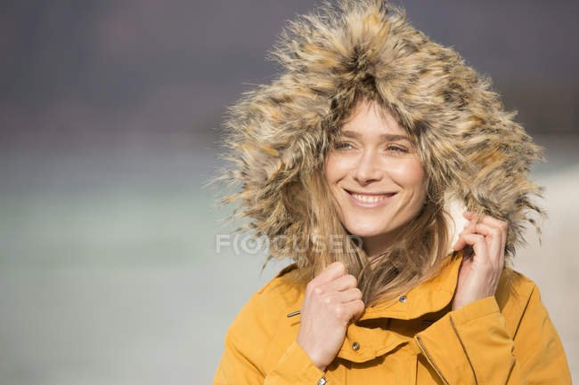 Portrait of mid adult woman outdoors, wearing fur trim coat, smiling — Stock Photo
