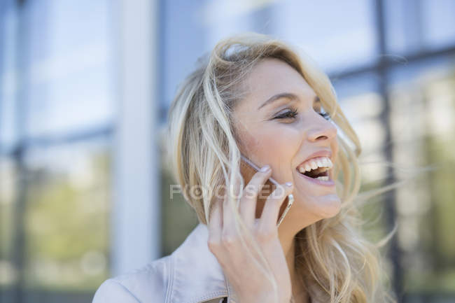 Young woman, outdoors, using smartphone, smiling — Stock Photo