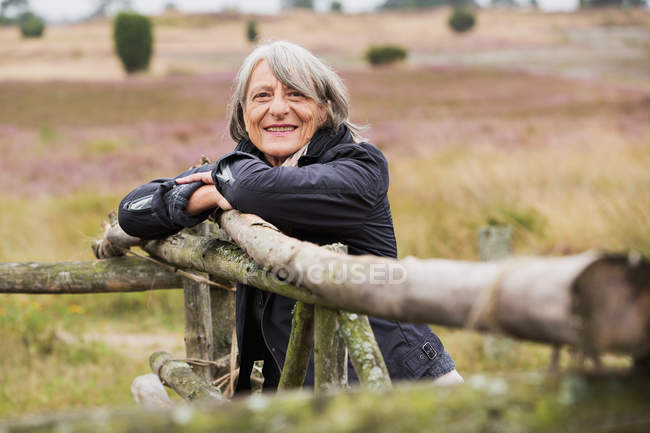Senior woman leaning on wooden fence smiling towards camera — Stock Photo