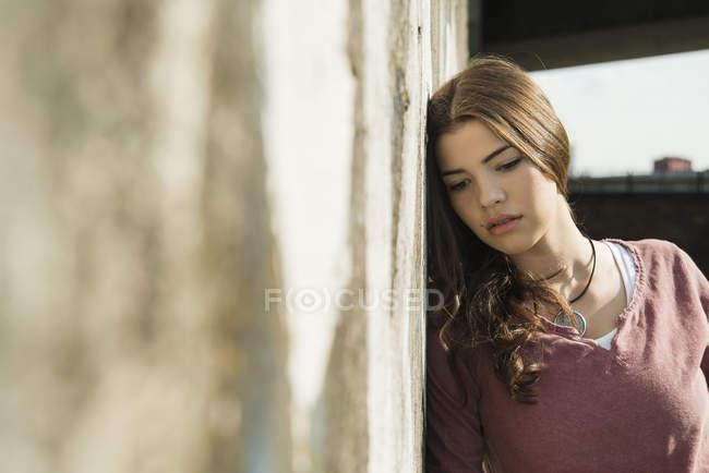 Молодая брюнетка, прислонившаяся к стене — стоковое фото