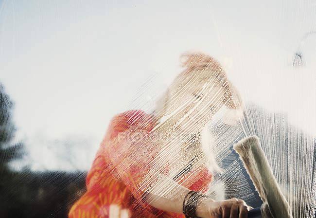 Mujer al aire libre limpiando ventana jabonosa con escobilla - foto de stock