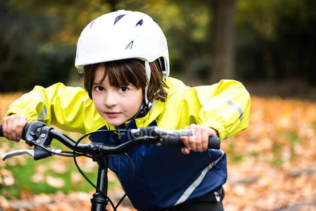 Boy con casco para bicicletas en bicicleta mirando a la cámara - foto de stock