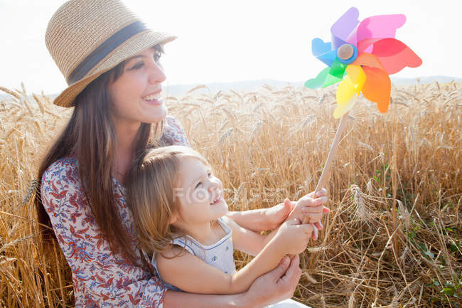 Mother and daughter in wheat field holding windmill — Stock Photo