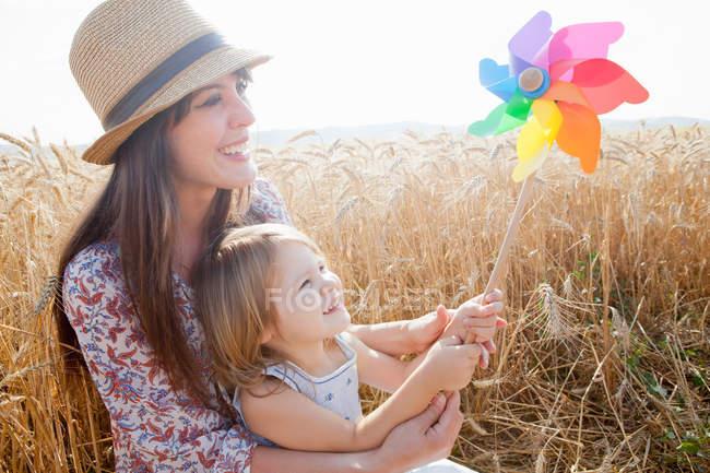 Мати і дочка в пшеничні поля холдингу млин — стокове фото
