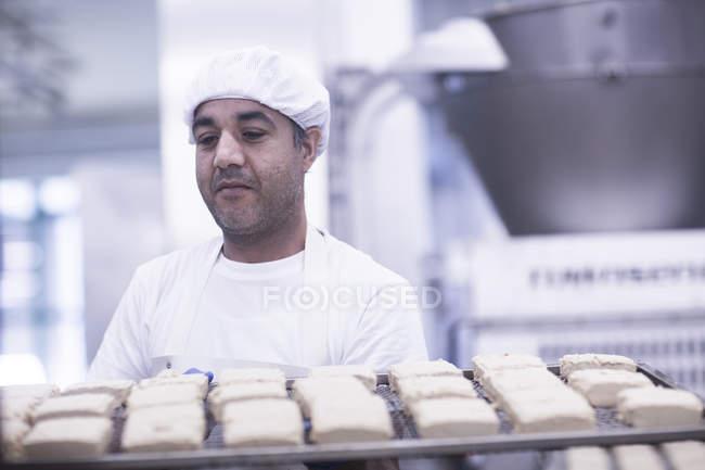 Hombre trabajando en fábrica de producción de alimentos llevando bandeja - foto de stock