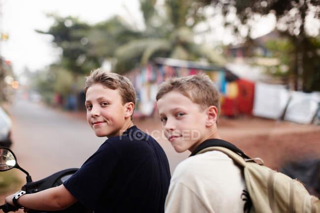 Adolescentes chicos montando scooter en camino de tierra - foto de stock