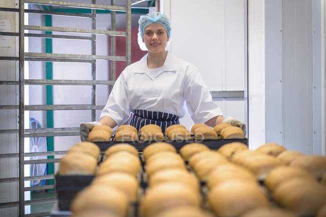 Baker segurando bandeja de pão cozido na hora, retrato — Fotografia de Stock