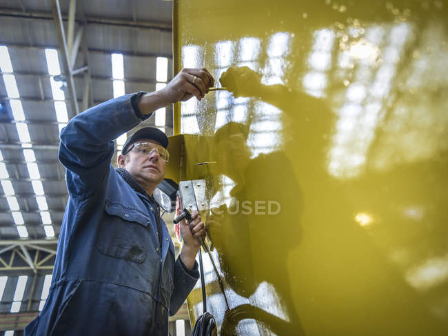 Worker on scaffolding in engineering factory, low angle view — Stock Photo