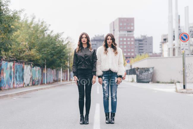 Ritratto di due sorelle gemelle, in area urbana, in piedi fianco a fianco — Foto stock