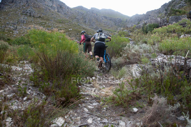 Молодая пара толкает горные велосипеды вверх по горе — стоковое фото