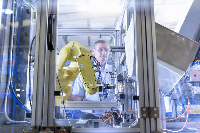 Ingenieur mit Roboter in Automobilteilefabrik — Stockfoto