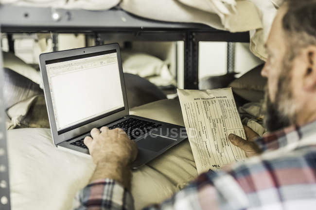 Scientist typing update from seed envelope in plant growth research centre warehouse — Stock Photo