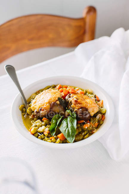Traditional Italian bowl of minestrone with artichokes, beans, carrots cheese and basil, Campania, Italy — Stock Photo